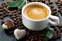 Tasse d'expresso sur des grains de café fond et bonbons au chocolat Image stock