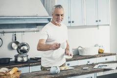 Tasse d'homme bel de café de offre de sourire à son épouse photographie stock libre de droits