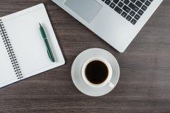 Tasse d'ordinateur portable, de carnet et de café sur le bureau de travail Images libres de droits