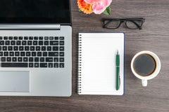 Tasse d'ordinateur portable, de carnet et de café sur le bureau de travail Photos stock