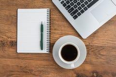 Tasse d'ordinateur portable, de carnet et de café sur le bureau de travail Photo libre de droits