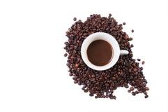 Tasse dans des haricots de coffe Photo stock
