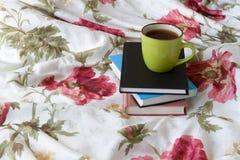 Tasse dans le lit avec le livre Photo libre de droits
