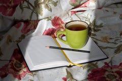 Tasse dans le lit avec le livre Photographie stock libre de droits