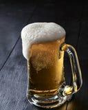 Tasse de bière avec de la bière de débordement écumeuse images stock