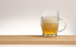 Tasse de bière blonde sur un conseil en bois photos libres de droits