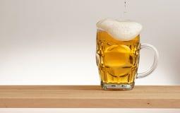 Tasse de bière blonde sur un conseil en bois photo stock