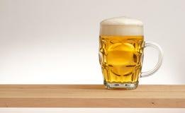 Tasse de bière blonde sur un conseil en bois image libre de droits