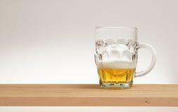 Tasse de bière blonde sur un conseil en bois photographie stock