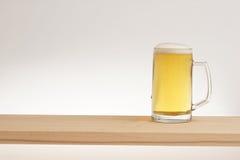 Tasse de bière blonde sur un conseil en bois images stock