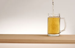 Tasse de bière blonde sur un conseil en bois image stock