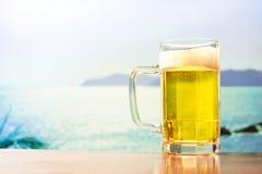Tasse de bière régénératrice sur la plage Photos stock