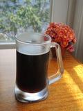 Tasse de bière foncée Images stock