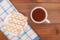 Tasse de biscuits de thé dans un plat Images stock