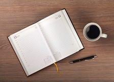 Tasse de bloc-notes et de café sur la table en bois Photo stock