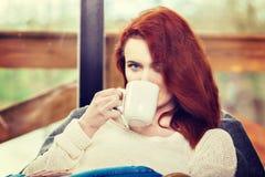 Tasse de boissons de femme d'Atractive de café rousse se reposant sur la chaise de basculage Jeune fille avec la boisson de activ Image stock