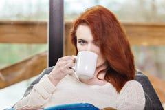 Tasse de boissons de femme d'Atractive de café rousse se reposant sur la chaise de basculage Jeune fille avec la boisson de activ Images libres de droits