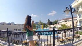 Tasse de boissons de jeune fille de café sur le balcon d'hôtel pendant des vacances d'été Femme regardant pensivement au-dessus d banque de vidéos