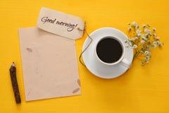 tasse de café à côté de papier blanc sur le fond jaune Photo libre de droits