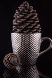 Tasse de café argentée Pimpled avec un grand pinecone à l'intérieur sur la surface noire réfléchie Et le deuxième petit pinecone Images stock