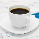 Tasse de café au-dessus de carte du monde et de quelques documents financiers - affaires image stock