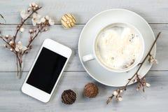 Tasse de café avec de la crème et le smartphone, sur la table en bois avec des fleurs et des bonbons au chocolat de cerise, vue s Images libres de droits