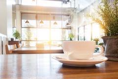 Tasse de café avec de la fumée sur la table en bois en café Image libre de droits