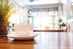 Tasse de café avec de la fumée sur la table en bois en café Photographie stock libre de droits