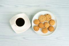 Tasse de café avec des biscuits de farine d'avoine du plat blanc Photographie stock libre de droits