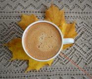 Tasse de café avec des feuilles et des châtaignes Photo stock