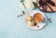 Tasse de café avec des fleurs et des chocolats Photographie stock