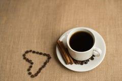 Tasse de café avec des grains de café sur la toile de jute Photographie stock libre de droits
