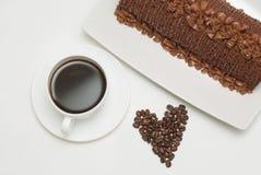 Tasse de café avec des grains de café en forme de coeur, d'isolement sur le fond blanc Photographie stock libre de droits