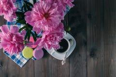 Tasse de café avec des macarons et de pivoine sur une table en bois photo libre de droits