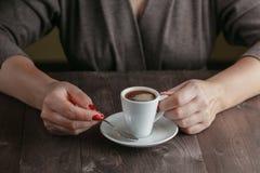 Tasse de café avec des mains sur la table à l'arrière-plan de café Photos stock