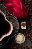 Tasse de café avec des pralines de chocolat et une rose rouge sur Roma en bois Image stock