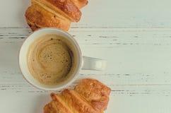 Tasse de café avec du lait et les croissants cuits au four frais Photographie stock