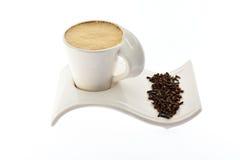Tasse de café avec du lait sur de belles graines et épices d'un grain de support Photographie stock libre de droits