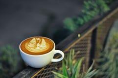Tasse de café avec l'art de latte sur la barrière en métal la nuit image libre de droits