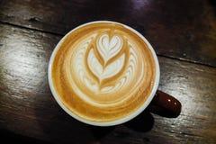 Tasse de café avec l'art de latte sur la table en bois Photos libres de droits