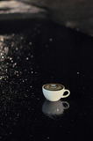 Tasse de café avec l'art de latte sur le plancher après avoir plu la nuit photos libres de droits