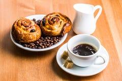 Tasse de café avec la cruche de cinnabon et de lait sur le fond en bois Photos stock
