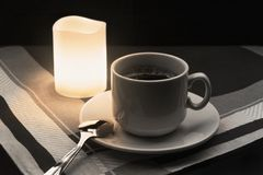 Tasse de café avec la cuillère et de bougie sur le fond de tissu photo stock