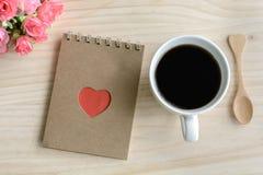 Tasse de café avec la fleur et le bloc-notes sur la table en bois Photos libres de droits