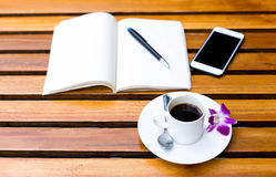 Tasse de café avec la fleur et le carnet sur la table Photos stock