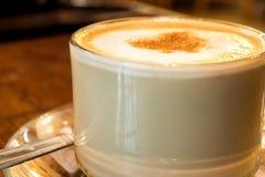 Tasse de café avec la mousse de lait sur la table en bois Images stock