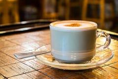 Tasse de café avec la mousse de lait sur la table en bois d'échecs Photographie stock libre de droits