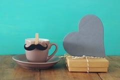 Tasse de café avec la moustache à côté du boîte-cadeau et du coeur en bois Father& x27 ; concept de jour de s Images stock