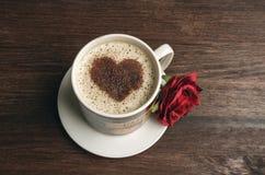 Tasse de café avec la rose de forme et de rouge de coeur sur le fond foncé Photographie stock libre de droits