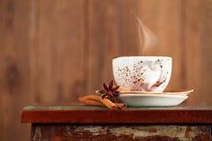 Tasse de café avec la vapeur, cannelle, anis sur un beau rustique Photographie stock libre de droits
